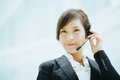 Attractive female Asian businesswoman wearing a headphones with microphone