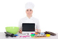 Attractive female confectioner in cook uniform sitting at the ki kitchen with laptop with copyspace isolated on white background Stock Photo