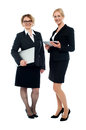 Attractive female executives full length shot studio of two businesswomen posing Stock Photos