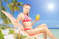 Attractive female holding a cocktail and sitting on a sun lounge lounger tropical beach next to sea palm trees Stock Photography