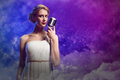 Attractive female singer with microphone a behind her abstract background Royalty Free Stock Photos