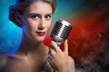 Attractive female singer with microphone a behind her abstract background Royalty Free Stock Image