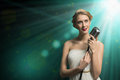 Attractive female singer with microphone a behind her abstract background Royalty Free Stock Images