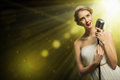 Attractive female singer with microphone a behind her abstract background Stock Photos