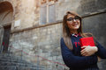 Attractive female student in glasses holding red bright book standing outdoors Royalty Free Stock Photo