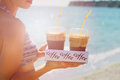 Attractive female waiters holding two ice frappe coffee on the beach near sea. Young woman enjoyng during summer holiday Royalty Free Stock Photo