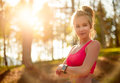 Attractive fit athletic woman in a forest, wearing smart watch, taking a break from intense workout. Sport, fitness, workout