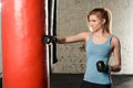Attractive fit blond girl in light blue tank top is hitting the red punching bag . Royalty Free Stock Photo
