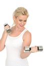 Attractive fit healthy happy young blonde woman working out with dumb bell weights in her twenties looking away from camera Stock Images