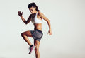 Attractive fit woman exercising in studio with copyspace image of healthy young female athlete doing fitness workout against grey Royalty Free Stock Image