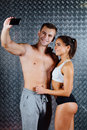 stock image of  Attractive fitness couple in sports clothes is making selfie indoor.