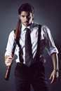 Attractive gangster with shotgun very fashion model dressed like a grey backdrop portrait Stock Photography