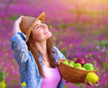 Attractive girl with apples basket young active gardener standing on floral field apple in hands and looking up on beautiful Royalty Free Stock Images
