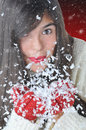 Attractive girl blowing snow closeup of an brunette out of her hands against a light to dark red background the is wearing Stock Photo