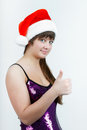 Attractive girl in a Christmas hat with thumb up Royalty Free Stock Photography