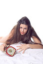 Attractive girl with desperate expression and old style alarm clock wake up concept Royalty Free Stock Photo