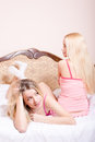 Attractive girl friends pretty cute young blond women in pink pajamas one of them is lying relaxing in bed two on her stomach Stock Image