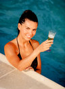 Attractive girl with a glass of champagne in the pool Stock Images