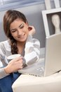 Attractive girl having tea by laptop Royalty Free Stock Photography