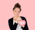Attractive girl with money box on a pink background Royalty Free Stock Photography