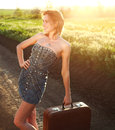 Attractive girl posing with suitcase at countryside on lonely road in sunset rays Stock Photography