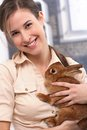 Attractive girl with rabbit portrait of smiling cuddling pet brown Royalty Free Stock Image