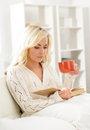 Attractive girl reading a book and having a cup of coffee in the morning Royalty Free Stock Photography
