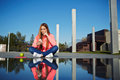 Attractive girl sitting next to the water with amazing reflection of her self Royalty Free Stock Photo