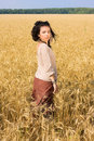 Attractive girl standing in wheat field Stock Photos