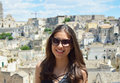Attractive girl with sunglasses in Matera, Unesco World Heritage Site and European Capital of Culture 2019. Smiling young woman tr Royalty Free Stock Photo