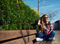 Attractive girl in sunglasses relaxing in the spring park while read book Royalty Free Stock Photo