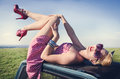 Attractive girl teasing female in short dress on car roof Royalty Free Stock Photos