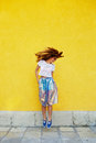 Attractive girl in an unusual skirt posing near a yellow wall Stock Images