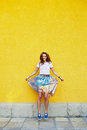 Attractive girl in an unusual skirt posing near a yellow wall Royalty Free Stock Photo