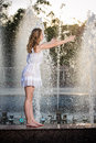 Attractive girl in white short dress sitting on parapet near the fountain in the summer hottest day with partly wet Royalty Free Stock Image