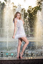 Attractive girl in white short dress sitting on parapet near the fountain in the summer hottest day with partly wet Royalty Free Stock Photography