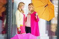 Attractive girlfreinds carrying the umbrellas colorful Stock Image