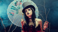 Attractive gothic girl in top hat with Chinese umbrella looking Royalty Free Stock Image