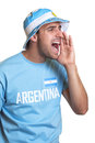Attractive guy with argentinian jersey and hat screaming for his team Royalty Free Stock Photo