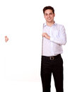 Attractive guy holding up a white placard portrait of an while standing and looking at you on isolated background copyspace Stock Photography