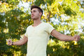 Attractive guy in the park extending his strong arms Royalty Free Stock Photo