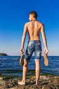 Attractive handsome sexy naked young man on rock near the sea wa Royalty Free Stock Photo