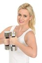 Attractive happy fit healthy young blonde woman working out with dumb bell weights in her twenties in front of chest looking at Royalty Free Stock Image