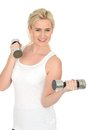 Attractive happy fit healthy young woman working out with dumb bell weights in her twenties looking determined looking at camera Royalty Free Stock Photography