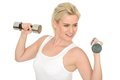 Attractive happy fit healthy young woman working out with dumb bell weights in her twenties looking determined to achieve fitness Royalty Free Stock Images