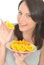 Attractive happy healthy natural young woman holding a plate of ripe juicy orange segments dslr royalty free image white fresh Royalty Free Stock Photos