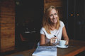 Attractive happy hipster girl with good mood is posing while sitting alone in modern coffee shop interior cheerful caucasian woman Stock Photography