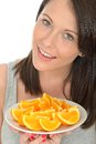 Attractive happy natural young woman holding a plate of ripe fresh orange segments dslr royalty free image smiling towards the Royalty Free Stock Image