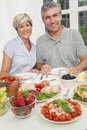 Attractive happy smiling middle aged couple healthy eating salad seafood cold meats fruit dining table Royalty Free Stock Photography