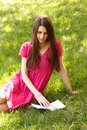 Attractive happy smiling student teen girl reading book outdoor on green spring grass Stock Photos